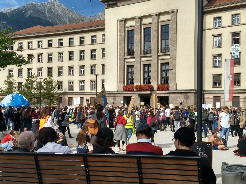 A gathering of people with protest signs in the plaza outside of Innsbruck town hall