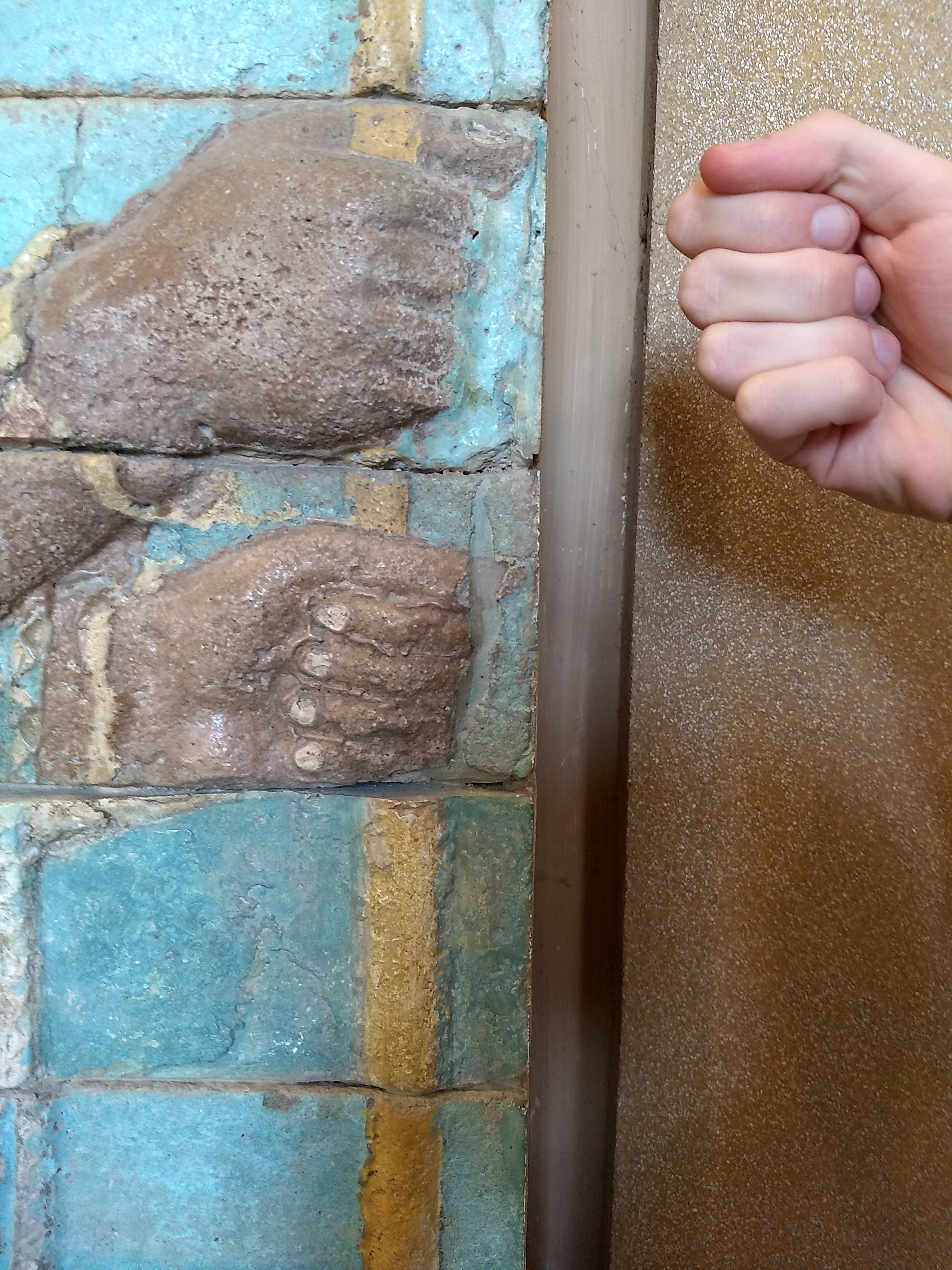 A glazed brick relief of a man holding a spear in both hands next to a clenched fist.  The fist gripping the spear and the live fist are aboout the same size.