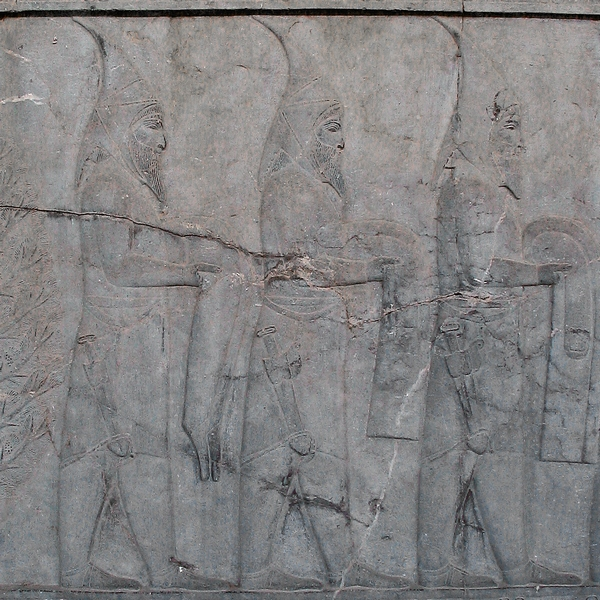 A relief of three delegates in pointed hoods, long coats, trousers and shoes with large daggers hanging at their right thighs.