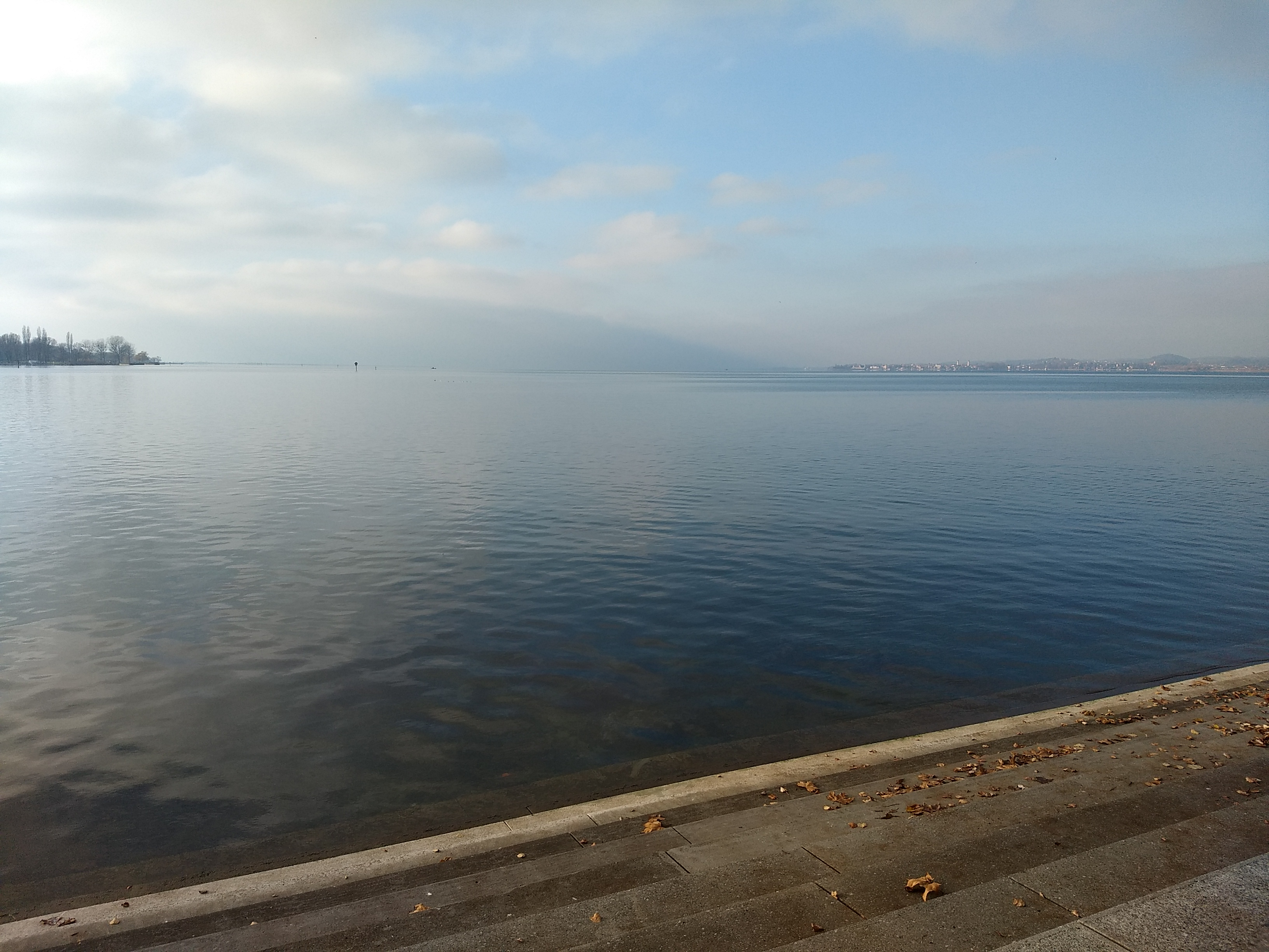 A view of a still lake and a cool sky from a stone breakwater