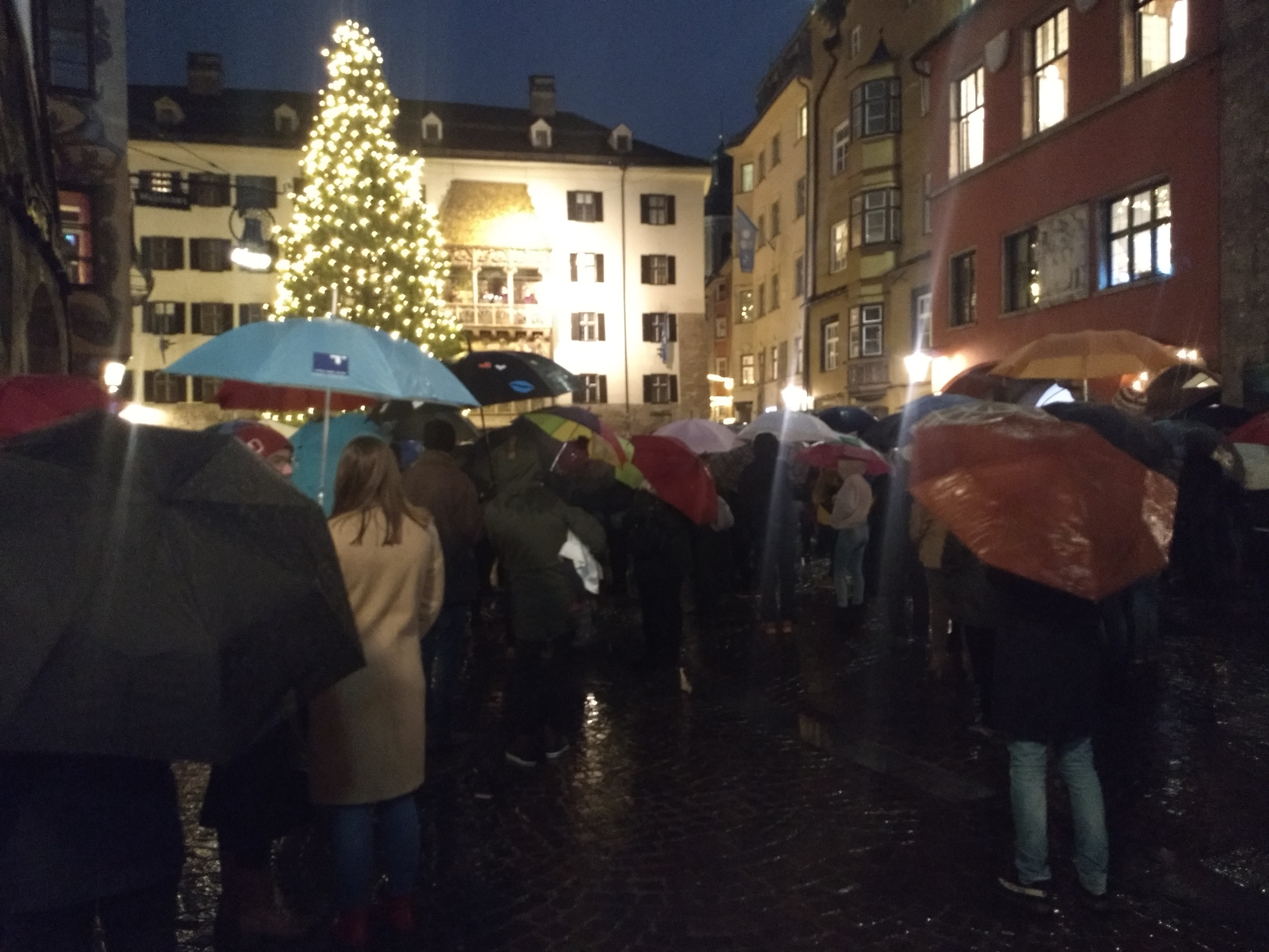 A crowd gathered in a rainy street in the medieval centre of Innsbruck