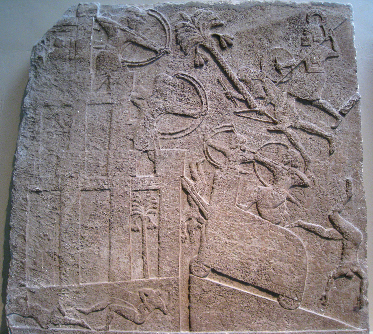 A wheeled battering ram with two spear-headed strikers and a tower climbs a ramp towards the wall of a three-leveled city while archers shoot back and forth and headless, naked corpses fall