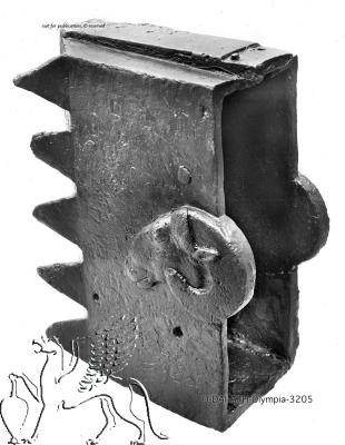 The hollow bronze head of a battering ram with a toothed striking surface and decorative rams' heads on the sides near the open back