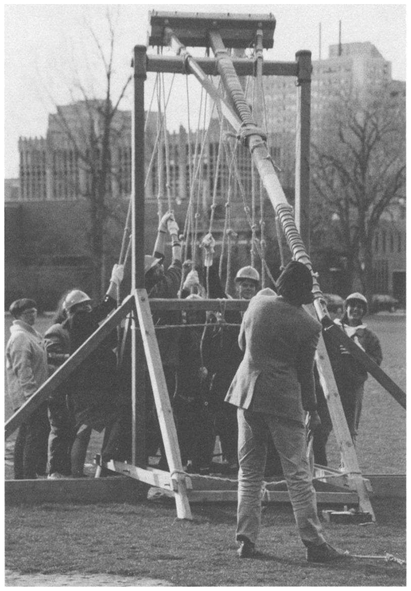 A professor in a suit takes aim while a team of volunteers prepares to pull the arm of a trebuchet