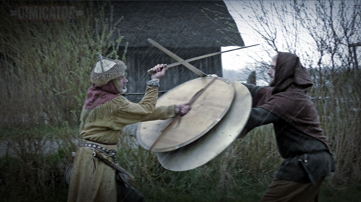 A bout with Viking shields and blunt swords.  One fenceruses the strange palm-up cut which was taught in late medival marital arts but not most other traditions.