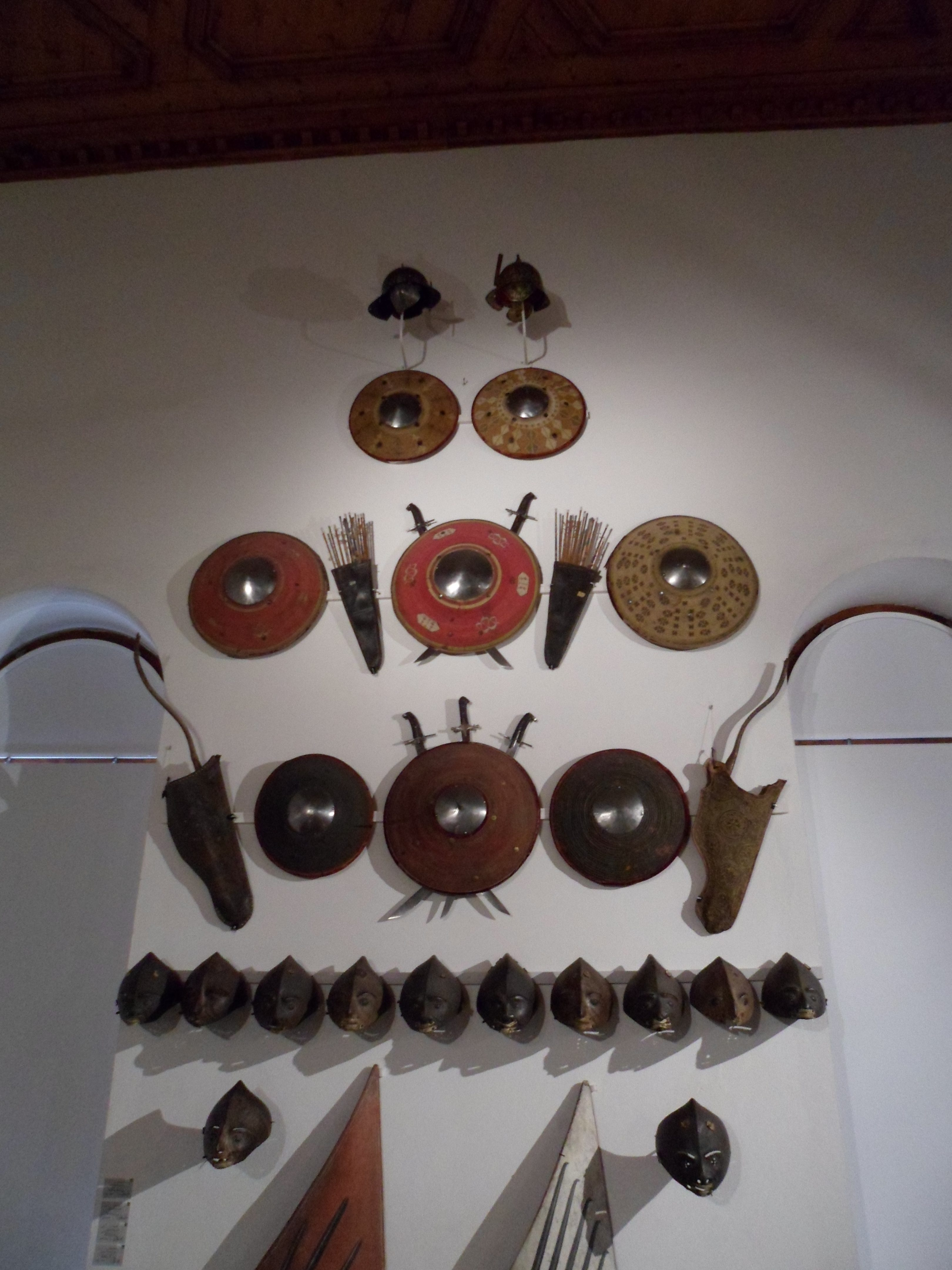 A display of wicker shields, helmets and face-masks, bows in bowcases, and sabres on a whitewashed wall