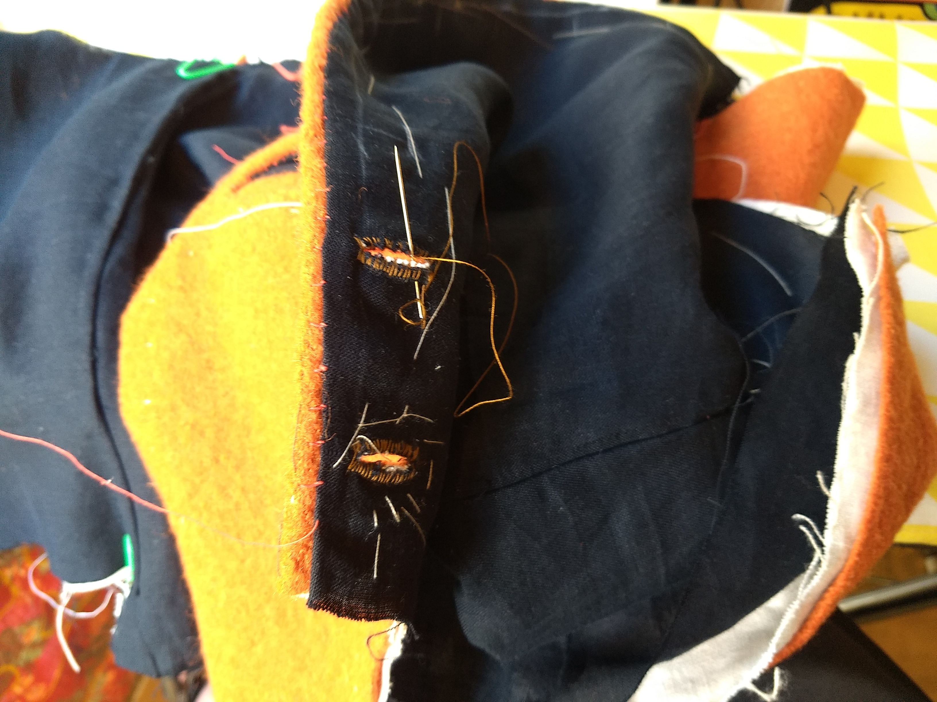 Buttonholes being sewed with silk to an orange woolen vest lined with black linen