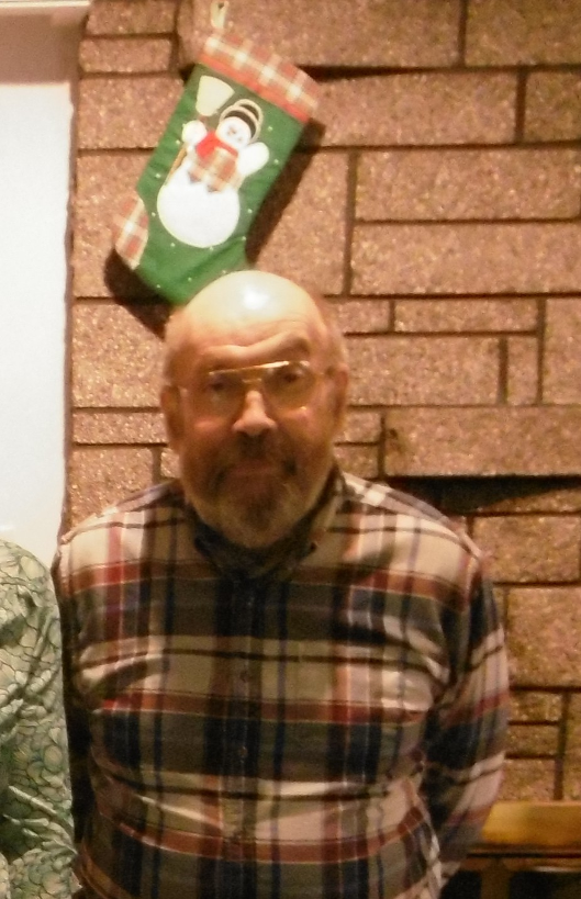 a photo of a short, bearded man in a checkered shirt standing in front of a stone fireplace with a Christmas stocking