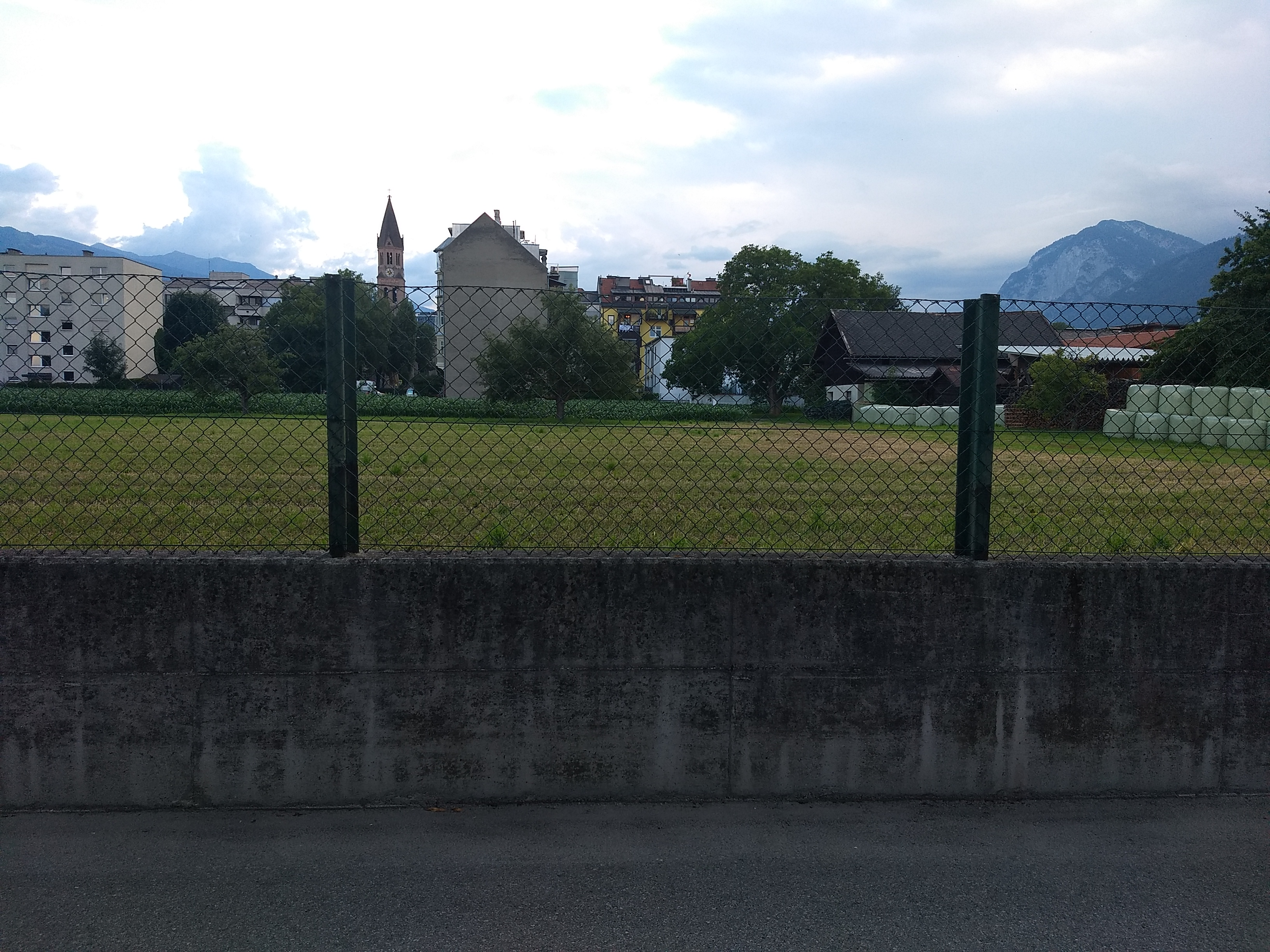 a photo of a farm with concrete and chain link fence in a European city centre