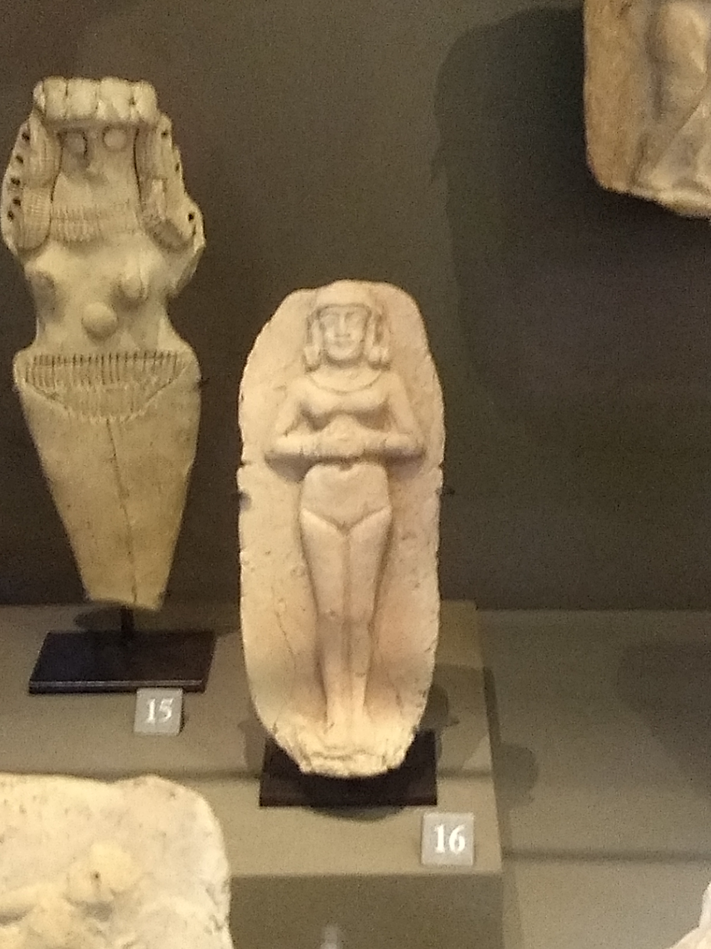 a plaque of a naked woman (or godess) standing with her hands clasped in front of her stomach