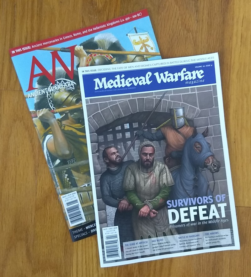 """an issue of """"ancient warfare"""" magazine and an issue of """"medieval warfare"""" magazine on a hardwood surface"""