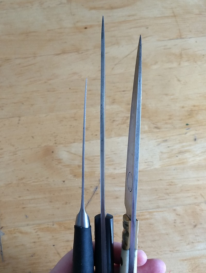 three knives held side by side in the hand over a wooden tabletop