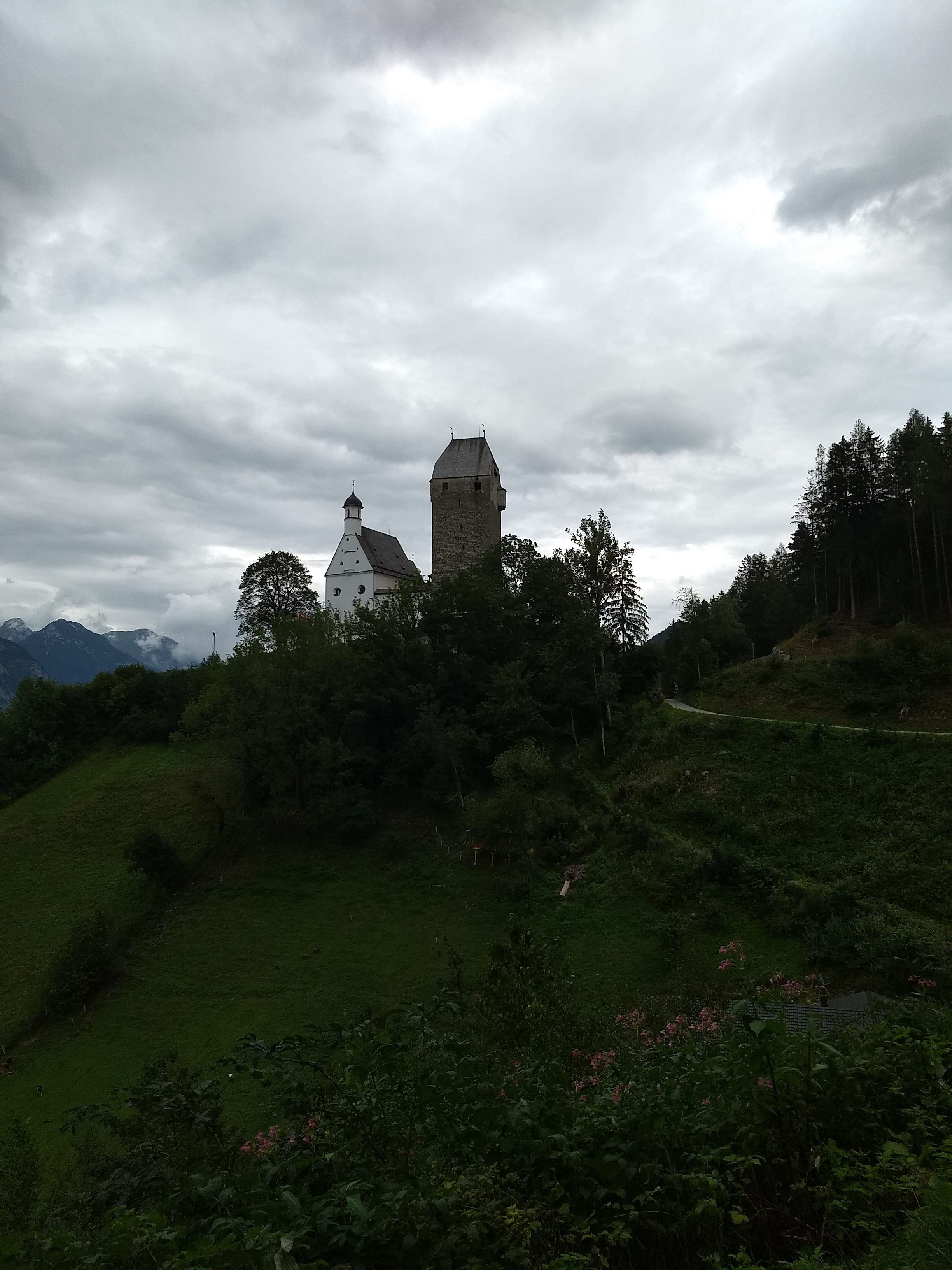 a keep and church atop a hill with cloudy sky in the background