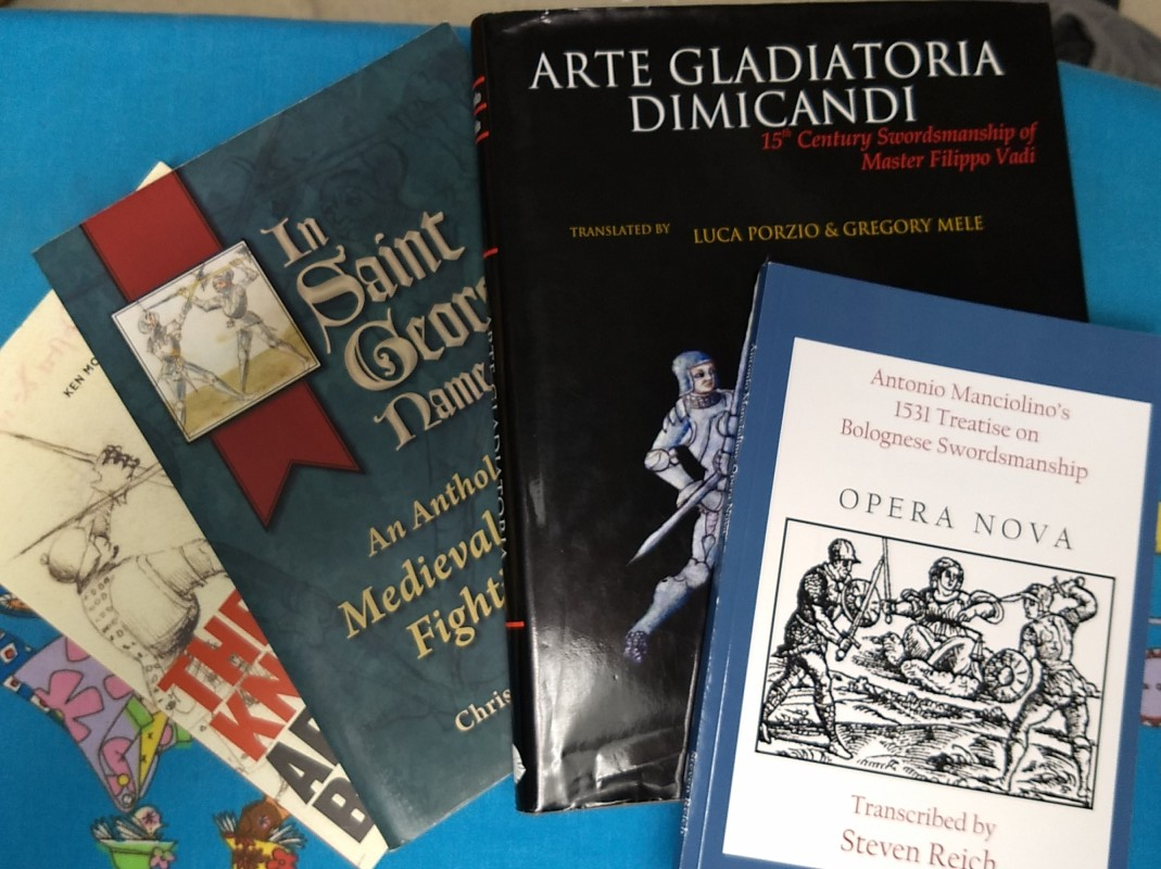 reprints of four early European fencing manuals on an ironing board covered with a colourful cotton print