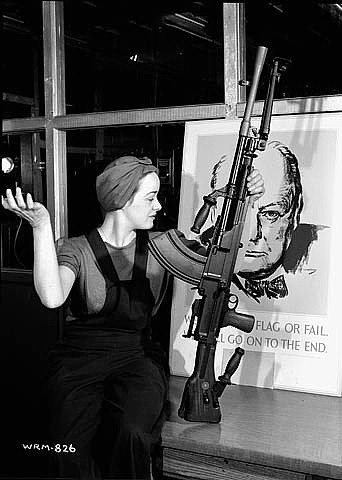 a woman in overalls and a bandana holds a newly completed light machine gun on a table in front of a poster