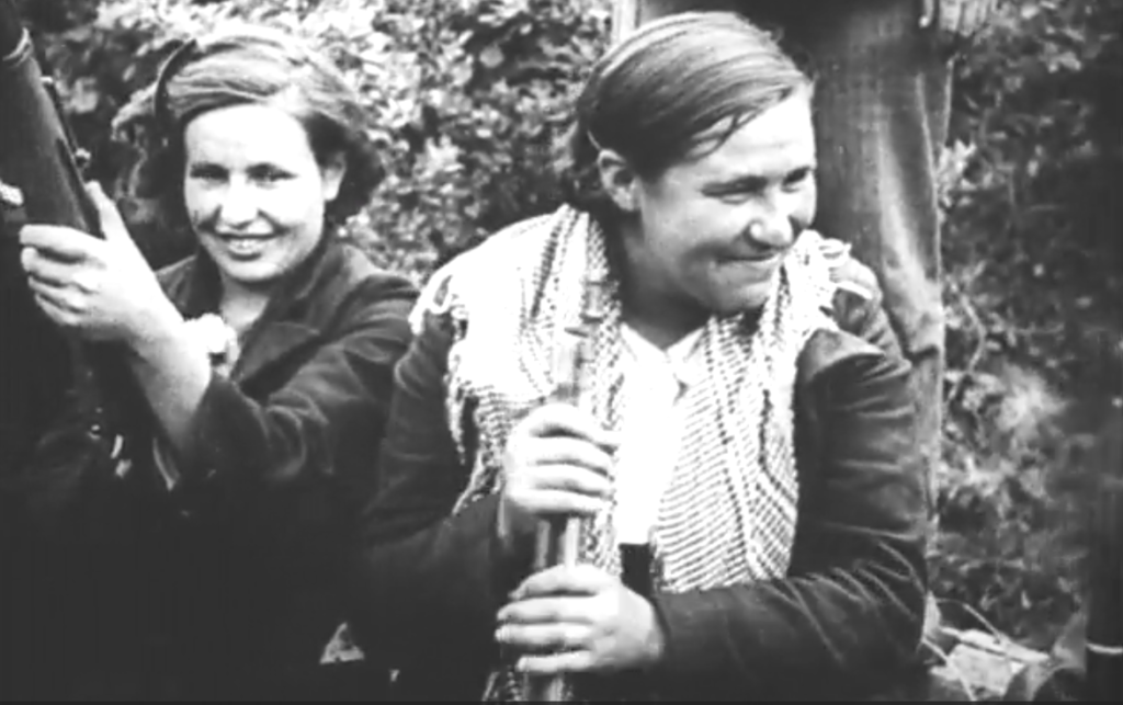 two smiling women with bolt-action rifles sitting in a wooded area