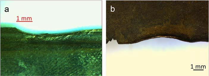 A magnified photo of the edges of two bronze swords, one verdegrised and one red